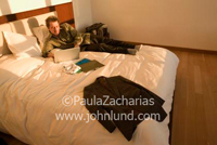 Business photo of a man working on his laptop while laying on the bed in his hotel room.  Clothing laid out on bed.
